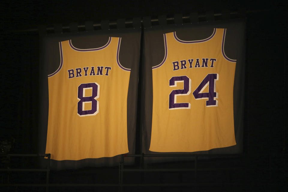 Los Angeles Lakers jersey numbers belonging to retired NBA player Kobe Bryant hang inside Staples Center prior to the start of the 62nd annual Grammy Awards on Sunday, Jan. 26, 2020, in Los Angeles.  Bryant, the 18-time NBA All-Star who won five championships during a 20-year career with the Los Angeles Lakers, died in a helicopter crash Sunday. He was 41.  (Photo by Matt Sayles/Invision/AP)