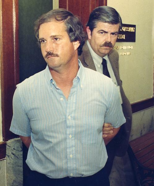 In this 1987 photo, Ed Graf is led away from judge's chambers by Hewitt police detective Frank Latham in Waco, Texas. Graf was given life in prison 25 years ago for killing his two stepsons by locking them in a backyard shed and setting it on fire. Two investigators used photos of the shed's remains to persuade jurors that Graf had started the fire intentionally killing Clare Bradburn's sons. Authorities in Texas and in other states are beginning to re-examine old arson cases in which defendants may have been convicted with questionable scientific evidence. (AP Photo/Waco Tribune Herald, Steve Earley)