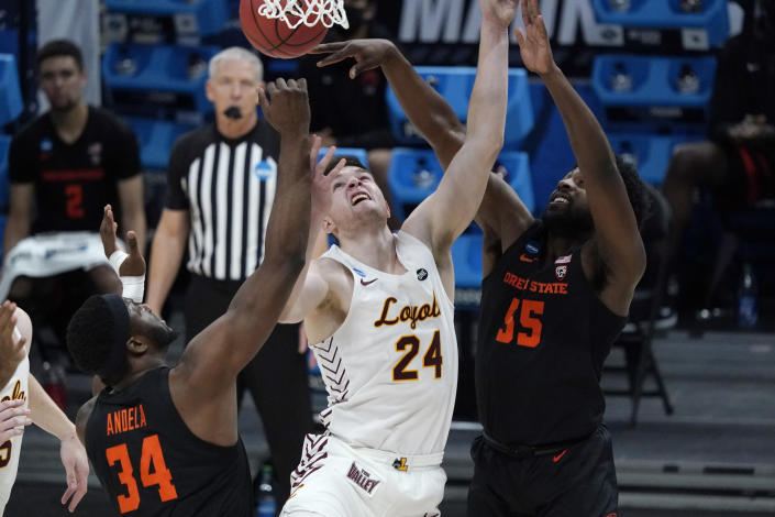 Loyola Chicago guard Tate Hall (24) drives to the basket between Oregon State forward Rodrigue Andela (34) and guard Tariq Silver (55) during the first half of a Sweet 16 game in the NCAA men's college basketball tournament at Bankers Life Fieldhouse, Saturday, March 27, 2021, in Indianapolis. (AP Photo/Jeff Roberson)