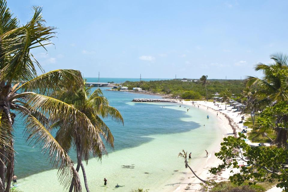 """<p>Perhaps one of the most Caribbean-style beaches in the mainland United States, <a href=""""http://bahiahondapark.com/"""" rel=""""nofollow noopener"""" target=""""_blank"""" data-ylk=""""slk:Bahia Honda State Park"""" class=""""link rapid-noclick-resp"""">Bahia Honda State Park</a> has it all: crystal-clear water, white sand beaches, and plenty of breezy palm trees. The island is located about three-fourths of the way down the Florida Keys at Mile Marker 37 on Big Pine Key. The water is so transparent that the snorkeling here is second to none. And be sure to check out what's left of Henry Flagler's historic Overseas Railroad—a great spot for sunset photos.</p>"""