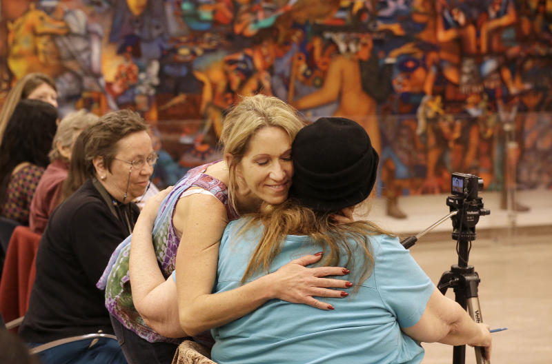 Sex worker Kristen D'Angelo, facing, hugs sex worker activist Carol Leigh at a meeting with others who claim that the California Victims Compensation Board discriminates against sex workers by denying them benefits after having been raped in San Francisco, Tuesday, Nov. 12, 2013. (AP Photo/Jeff Chiu)