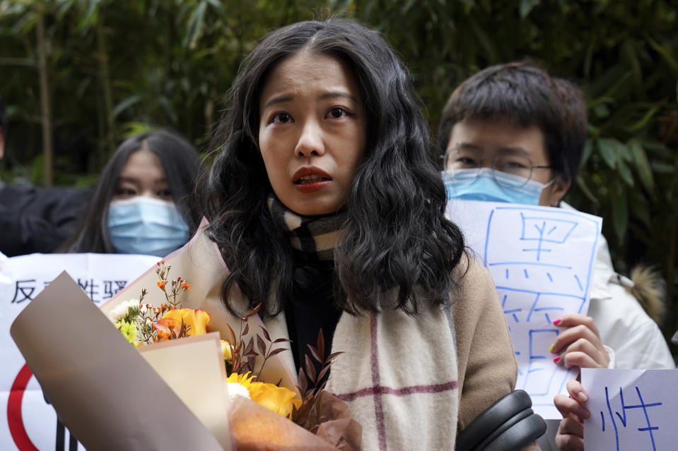 Zhou Xiaoxuan, center, speaks to her supporters holding banners as she arrives at a courthouse in Beijing, Wednesday, Dec. 2, 2020. Zhou, a Chinese woman who filed a sexual harassment lawsuit against a TV host, told dozens of cheering supporters at a courthouse Wednesday she hopes her case will encourage other victims of gender violence in a system that gives them few options to pursue complaints.(AP Photo/Andy Wong)