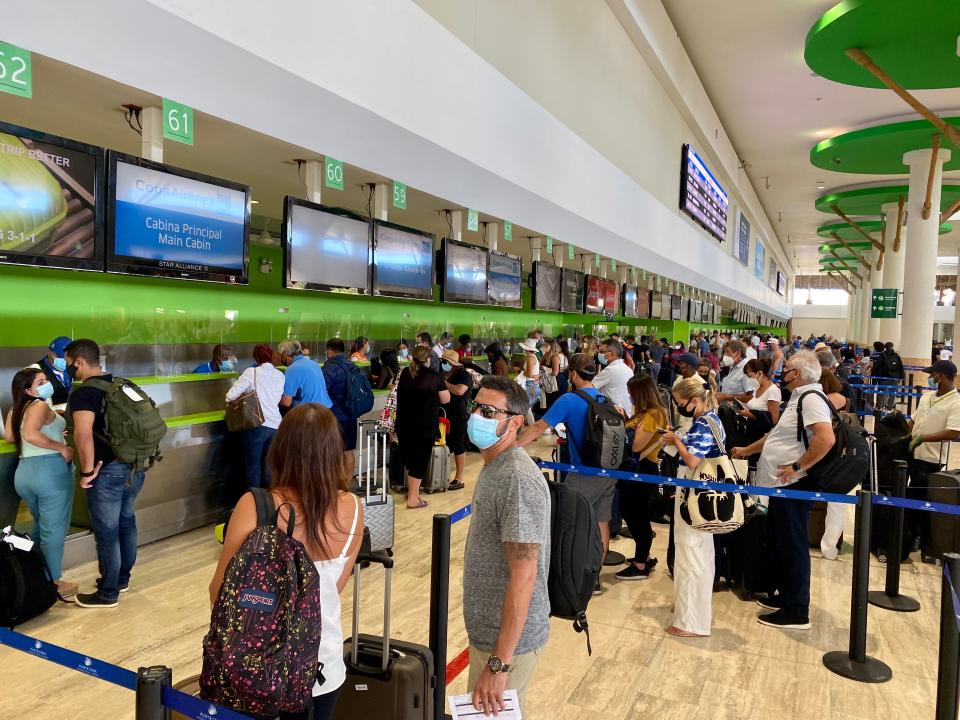 Tourists wait fot their turn at the counters at the Punta Cana International Airport (PUJ), in Dominican Republic on December 5, 2020 amid the covid-19 coronavirus pandemic. (Photo by Daniel SLIM / AFP) (Photo by DANIEL SLIM/AFP via Getty Images)