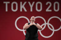 """Laurel Hubbard of New Zealand says """"Thank you"""" and bows after a lift, in the women's +87kg weightlifting event at the 2020 Summer Olympics, Monday, Aug. 2, 2021, in Tokyo, Japan. (AP Photo/Luca Bruno)"""