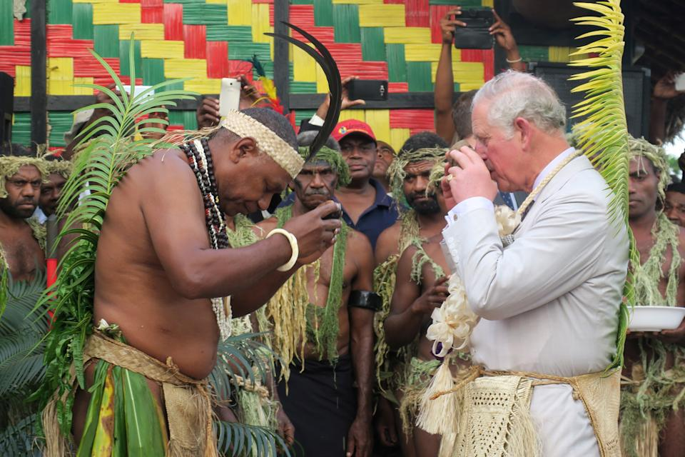 Britain's Prince Charles (R) drinks kava with Chief Seni Mao Tirsupe, the President of the Malvatumauri Council of Chiefs, to the Chiefs Nakamal in Port Vila on April 7, 2018.            / AFP PHOTO / Ben BOHANE        (Photo credit should read BEN BOHANE/AFP via Getty Images)