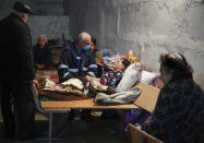 A medical worker talks to a sick woman in a bomb shelter in Stepanakert, the separatist region of Nagorno-Karabakh, Thursday, Oct. 22, 2020. Heavy fighting over Nagorno-Karabakh continued Thursday with Armenia and Azerbaijan trading blame for new attacks, hostilities that raised the threat of Turkey and Russia being drawn into the conflict. (AP Photo)