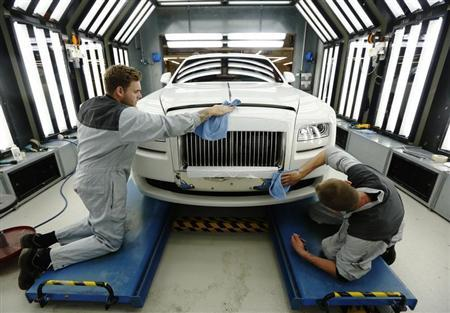 Employees Joe Don and Darren Lowarson give a Rolls Royce Ghost its final finish polish at the Rolls Royce Motor Cars factory at Goodwood near Chichester