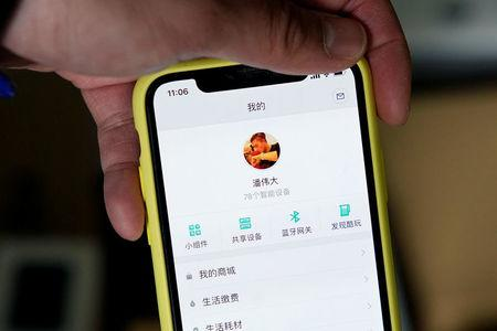 Pan Weida shows Xiaomi's app on his phone in Shanghai