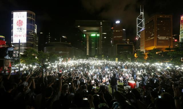 """Pro-democracy protesters switch on their mobile phones during a campaign to kick off the Occupy Central civil disobedience event in front of the financial Central district in Hong Kong August 31, 2014. China's parliament said on Sunday it will tightly control the nomination of candidates for a landmark election in Hong Kong in 2017. Thousands of """"Occupy Central"""" activists, who are demanding Beijing allow a real, free election, are threatening to blockade the city's business district in retaliation as part of a campaign of civil disobedience. REUTERS/Bobby Yip (CHINA - Tags: POLITICS TPX IMAGES OF THE DAY)"""