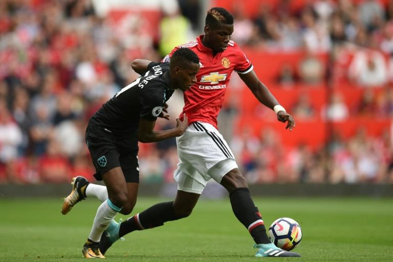 West Ham United's midfielder Edimilson Fernandes (L) vies with Manchester United's midfielder Paul Pogba during the English Premier League football match August 13, 2017
