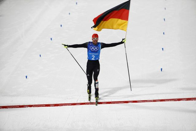 Nordic Combined Events - Pyeongchang 2018 Winter Olympics - Men's Team 4 x 5 km Final - Alpensia Cross-Country Skiing Centre - Pyeongchang, South Korea - February 22, 2018 - Johannes Rydzek of Germany waves the German flag as he crosses the finish line. REUTERS/Dominic Ebenbichler