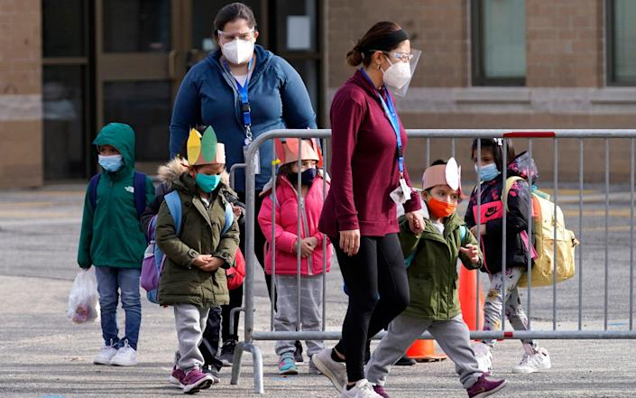 Students walk to a school bus with teachers after in-person classes at school - AP