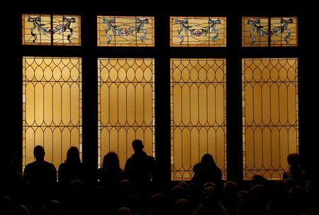 People stand against windows during a vigil held at All Souls Unitarian Universalist Church the day after a gunman opened fire on a Planned Parenthood clinic in Colorado Springs, Colorado November 28, 2015. REUTERS/Isaiah J. Downing