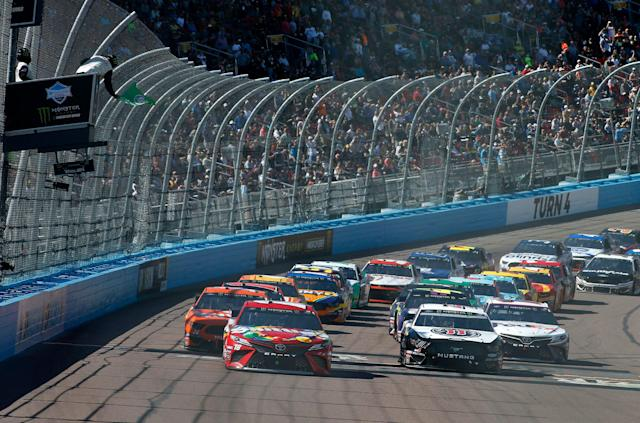 Kyle Busch (18) and Kevin Harvick (4) lead the field to the green flag on a restart during the NASCAR Cup Series auto race at ISM Raceway, Sunday, March 10, 2019, in Avondale, Ariz. (AP Photo/Ralph Freso)