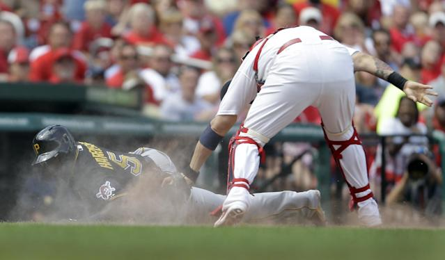 Pittsburgh Pirates' Josh Harrison, left, falls as he is tagged out by St. Louis Cardinals catcher Yadier Molina after being caught between third and home when Neil Walker reached on a fielder's choice during the seventh inning of a baseball game Thursday, Aug. 15, 2013, in St. Louis. (AP Photo/Jeff Roberson)