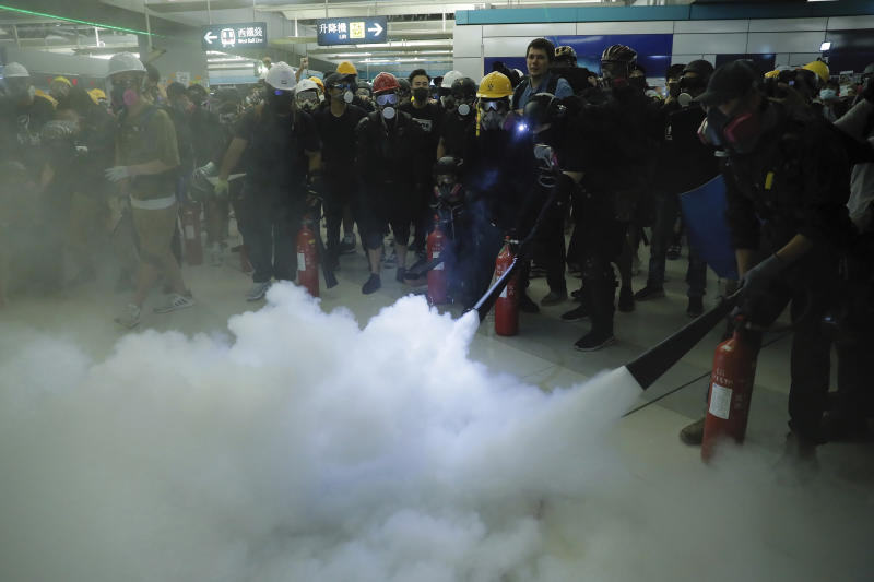Demonstrators spray fire extinguishers during a protest at the Yuen Long MTR station in Hong Kong, Wednesday, Aug. 21, 2019. Hong Kong riot police faced off with protesters occupying a suburban train station Wednesday evening following a commemoration of a violent attack there by masked assailants on supporters of the anti-government movement. (AP Photo/Kin Cheung)