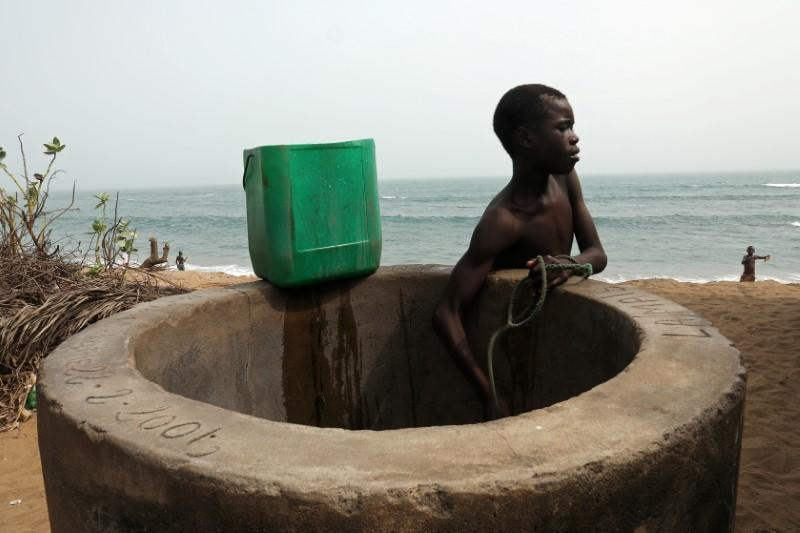 A boy takes water from a well on a sandy beach that is being lost through sea storms and coastal erosion in Baguida