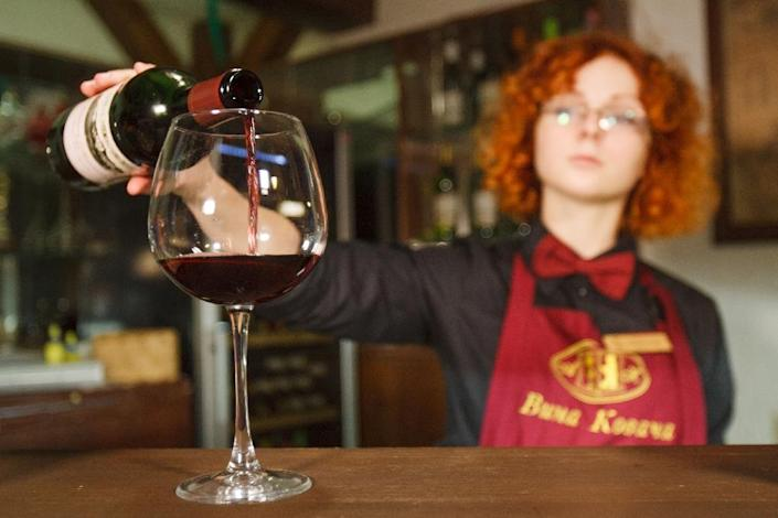 A bartender pours a glass of wine for tourists during a tasting session as Ukraine's revived wine industry is also boosting tourism. (AFP Photo/Sergiy GUDAK)