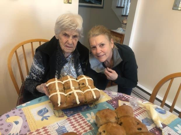 Mai Gosselin and her daughter, Pierrette McKnight, with a fresh batch of hot cross buns. The Moncton family has been baking them for decades. (Submitted by Pierrette McKnight - image credit)