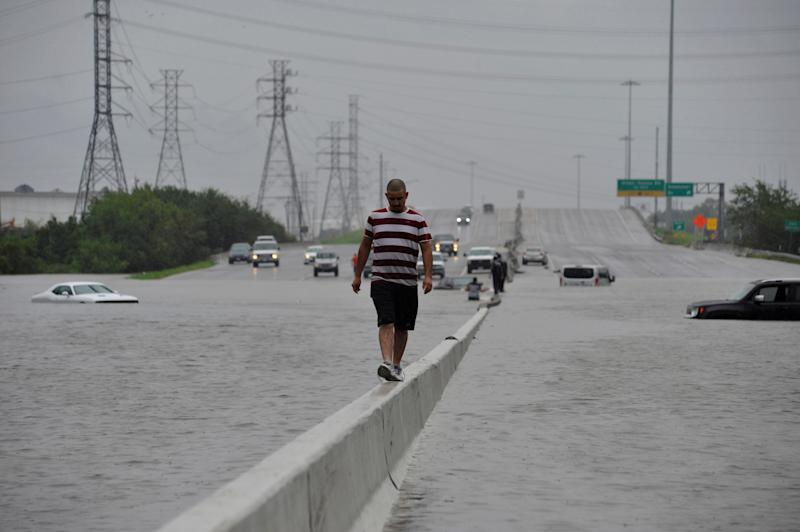 A stranded motorist escapes floodwaters on Interstate 225 in Houston on Sunday. (Nick Oxford/Reuters)