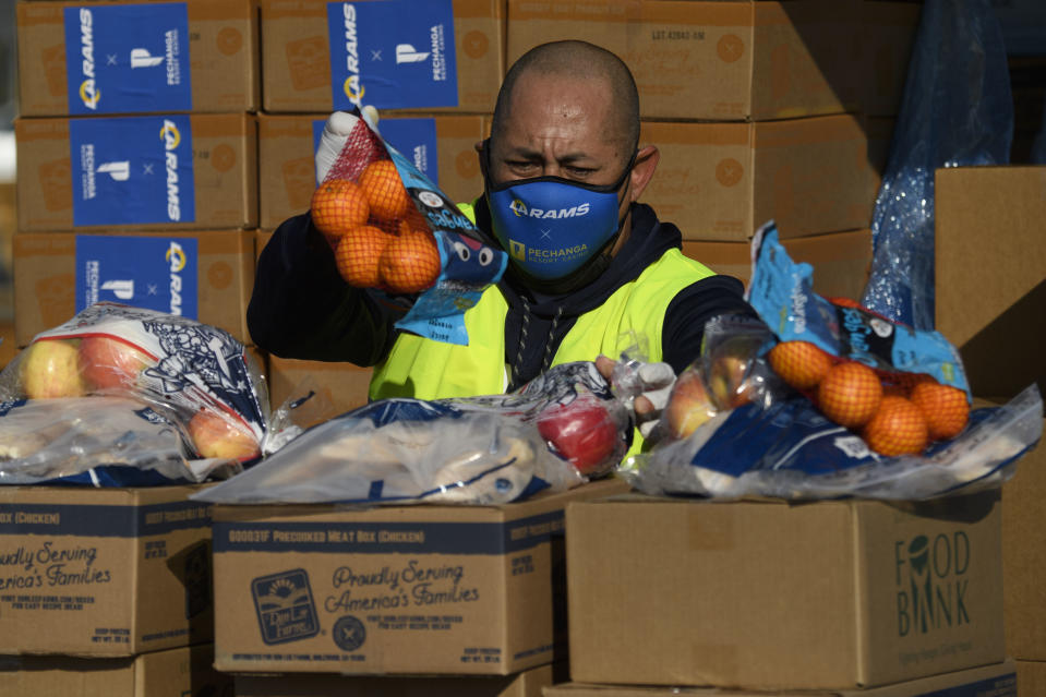 A volunteer wearing a face mask organizes groceries to load into vehicles during a holiday mobile food distribution from the Los Angeles Regional Food Bank supported by the Los Angeles Rams NFL football team and Pechanga Resort Casino outside of SoFi Stadium on December 22, 2020 in Inglewood, California. - The Los Angeles Regional Food Bank has distributed 145 million pounds of food since the Covid-19 pandemic started. (Photo by Patrick T. Fallon / AFP) (Photo by PATRICK T. FALLON/AFP via Getty Images)