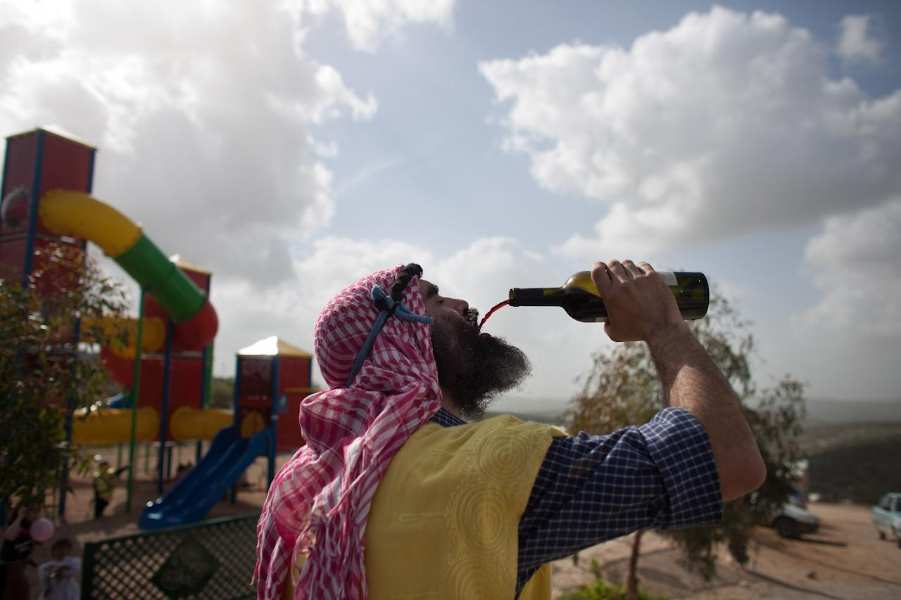 HAVAT GILAD, WEST BANK - FEBRUARY 24: (ISRAEL OUT) A Jewish settlers wears a costume as he drinks wine as settlers celebrate the Jewish festival of Purim February 24, 2013 at the settlement outpost of Havat Gilad, West Bank. The carnival-like Purim holiday is celebrated with parades and costume parties to commemorate the deliverance of the Jewish people from a plot to exterminate them in the ancient Persian empire 2,500 years ago, as described in the Book of Esther. (Photo by Uriel Sinai/Getty Images)Ê