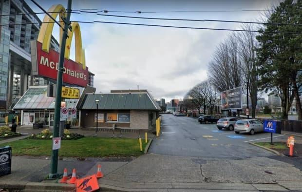 The VPD says the driver dropped something from his vehicle when paying at a McDonalds drive-thru and died after his vehicle rolled and crushed him against part of the building at the intersection of Main and Terminal Streets in East Vancouver. (Google Maps - image credit)