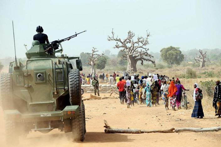 A Nigerian army armoured vehicle gives cover to Chibok women as they walk along a road in northeastern Nigeria, on March 5, 2015 (AFP Photo/Sunday Aghaeze)