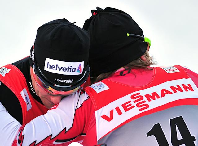 Canada's Devon Kershaw (R) is embraced by Swiss Dario Cologna (L) after winning the1,3 km Sprint Men men's event of the FIS World Cup Tour De Ski on January 5, 2011 in Toblach-Dobbiaco. Kershaw won the event ahead of Cologna and Norwegian Petter Northug. AFP PHOTO / ALBERTO PIZZOLI (Photo credit should read ALBERTO PIZZOLI/AFP/Getty Images)