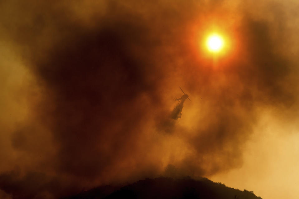 FILE - In this Monday, Aug. 17, 2020 file photo, a helicopter drops water while battling the River Fire in Salinas, Calif. Fire crews across the region scrambled to contain dozens of blazes sparked by lightning strikes during a statewide heat wave. According to data released by the National Oceanic and Atmospheric Administration on Tuesday, May 4, 2021, the new United States normal is not just hotter, but wetter in the eastern and central parts of the nation and considerably drier in the West than just a decade earlier. (AP Photo/Noah Berger)