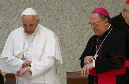Pope Francis and an unidentified bishop look at their watches during a special audience to mark the 50th anniversary of Synod of Bishops in Paul VI hall at the Vatican October 17, 2015. REUTERS/Tony Gentile