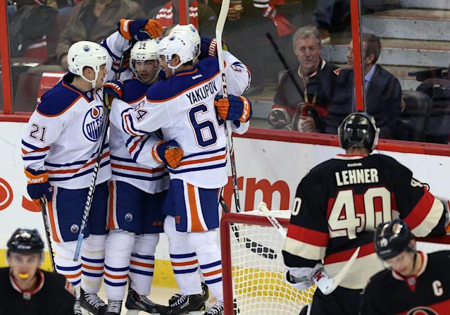 Edmonton Oilers' Jordan Eberle (14) celebrates his goal with teammates Nail Yakupov (64) and Andrew Ference (21) during the first period of an NHL hockey against the Ottawa Senators in Ottawa, Saturday, Oct. 19, 2013. (AP Photo/The Canadian Press, Fred Chartrand)