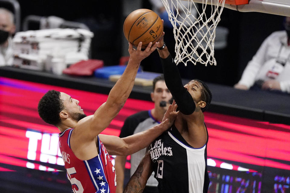 Philadelphia 76ers guard Ben Simmons, left, shoots as Los Angeles Clippers guard Paul George defends during the first half of an NBA basketball game Saturday, March 27, 2021, in Los Angeles. (AP Photo/Mark J. Terrill)