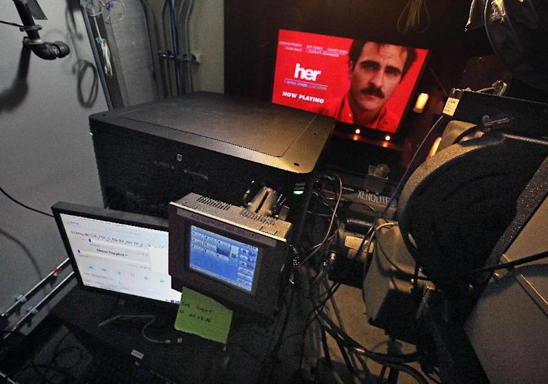 """In this April 4, 2014 photo, a digital cinema projector runs a trailer for the movie """"Her"""" at the three-screen SIE Film Center, a movie theater run by the Denver Film Society, in Denver. As movie theaters small and large are increasingly obliged to upgrade their systems from actual film to expensive digital movie projection, Denver Film Society, the Gates Family Foundation and others are offering grants to small-town locally owned theaters so they can afford the transition. (AP Photo/Brennan Linsley)"""