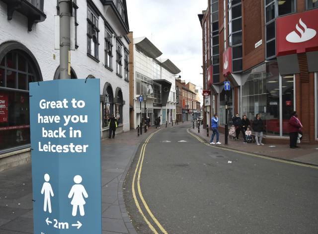 People walk through Leicester city centre as the government reimposed lockdown restrictions. (AP)