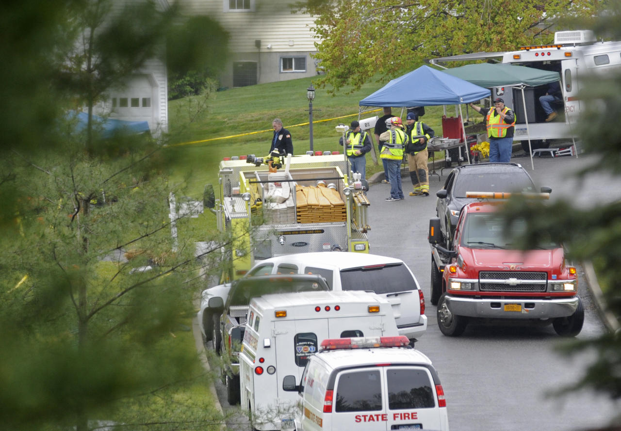 Fire Department personnel set up a temporary station near the hidden from view destroyed home on Wyndham Lane Tuesday, May 1, 2012, in Carmel, N.Y. A police captain, his wife and two teenage daughters died in a fire that swept through their home early Tuesday. Larchmont, N.Y. police identified the dead as Thomas Sullivan of the Larchmont police, his wife, Donna, and their two daughters. A son escaped from the burning Carmel home in Putnam County, about 60 miles north of New York City. (AP Photo/Louis Lanzano)