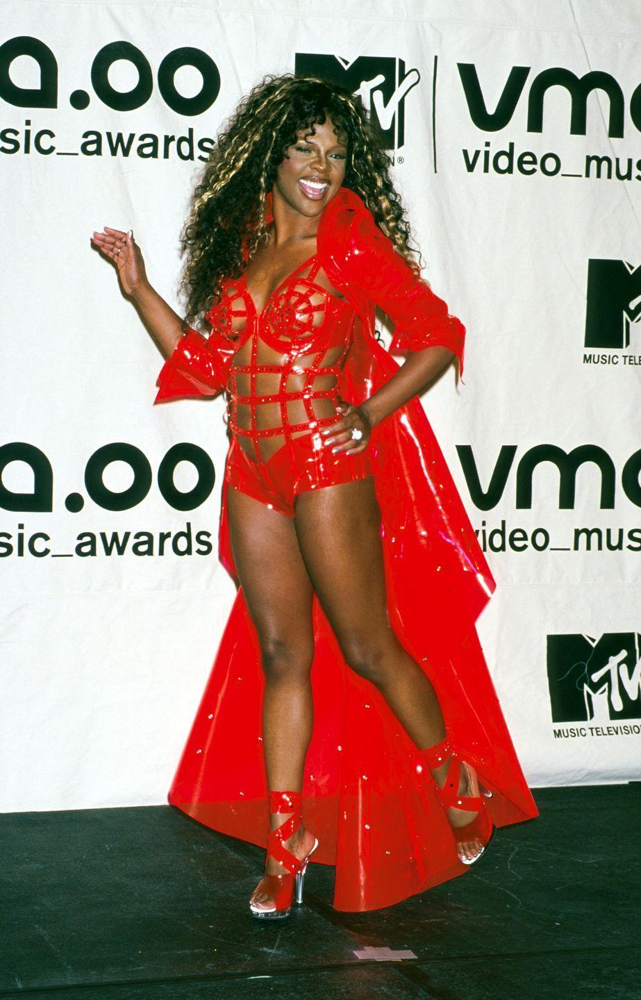 <p>The following year, Lil Kim continued the red carpet shock factor in this PVC, scarlet caged leotard and matching coat.</p>