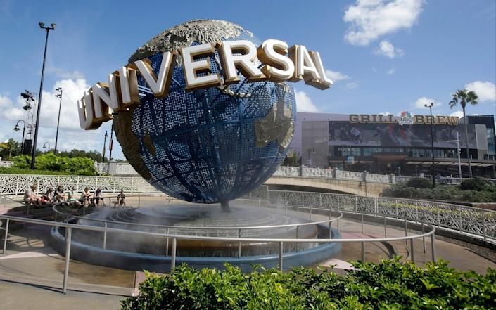n this Thursday, Oct. 22, 2015 file photo, park guests relax and cool off with a water mist under the globe at Universal Studios City Walk in Orlando, Fla. Universal Orlando Resort and SeaWorld are the latest theme park resorts in Florida to again ask visitors to wear masks indoors, with Universal also ordering its employees to wear face coverings to protect against COVID-19, which has been surging across the state. All workers at Universal's Florida park on Saturday, July 31, 2021 started being required to wear masks while indoors as the employees returned to practicing social distancing. - AP