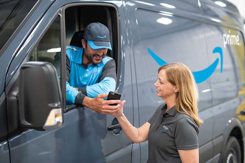 A uniformed driver in an Amazon-branded delivery van showing a smartphone to an Amazon employee standing outside.