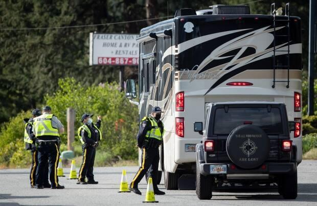 An RCMP officer speaks with a motorist in a recreational vehicle travelling to Alaska at a COVID-19 checkpoint on May 7.   (Darryl Dyck/The Canadian Press - image credit)