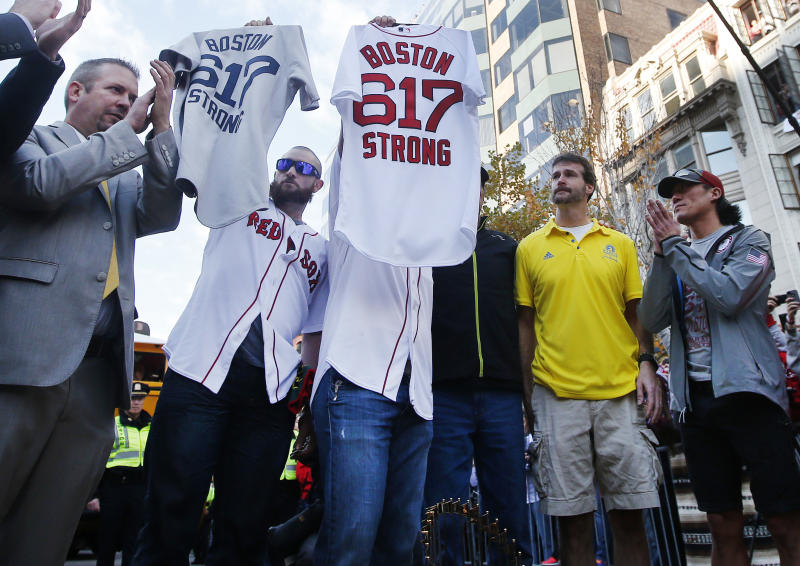 Boston Red Sox's Jonny Gomes, second from left, and Jarrod Saltalamacchia hold up baseball jerseys during a pause in their World Series victory rolling rally in Boston, Saturday, Nov. 2, 2013, to remember those affected by the Marathon bombing. They presented the jerseys to workers at two of the businesses at the bombing sites, including, second from right, Shane O'Hara and at far right, Dan Solo. (AP Photo/Elise Amendola)