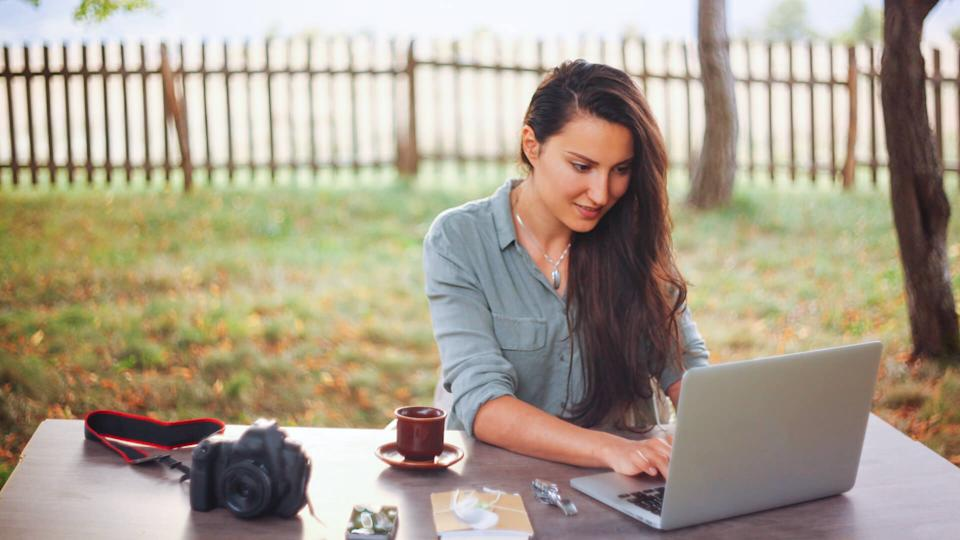 Smiling female novelist, blogger, freelancer or a photographer, typing on the laptop keyboard while having a cup of coffee, sitting in the bright outdoors at the desk.