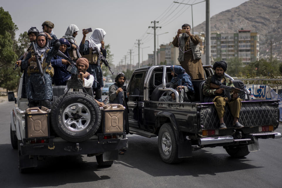 Taliban fighters escort women's march in support of the Taliban government outside Kabul University, Afghanistan, on Saturday, Sept. 11, 2021. (AP Photo/Bernat Armangue)