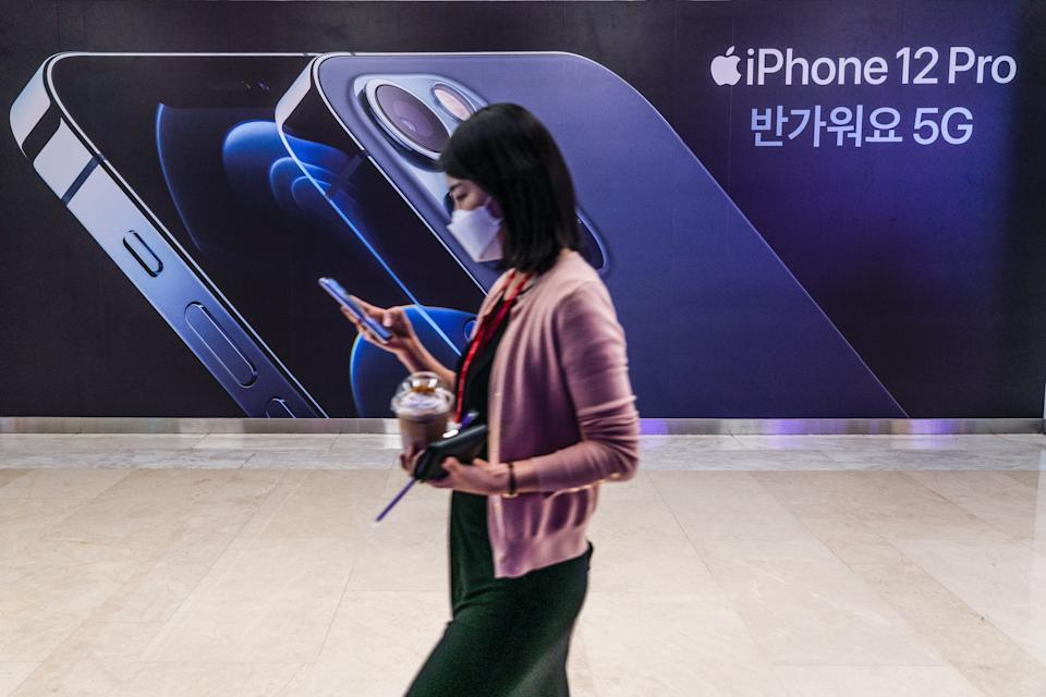 SEOUL, SOUTH KOREA - 2020/11/13: A woman wearing a mask walks past an iPhone 12 advertisement in Seoul. (Photo by Simon Shin/SOPA Images/LightRocket via Getty Images)
