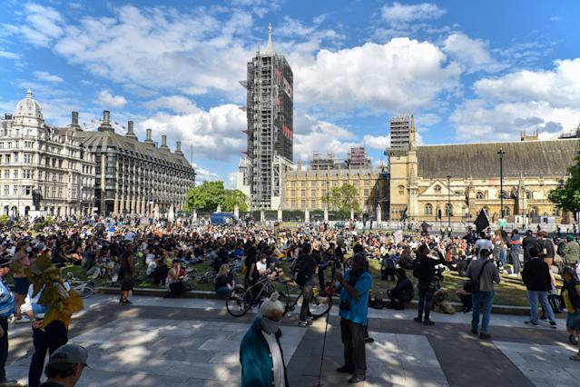 Black Lives Matter protesters sit in front of the Houses of Parliament. (Getty)