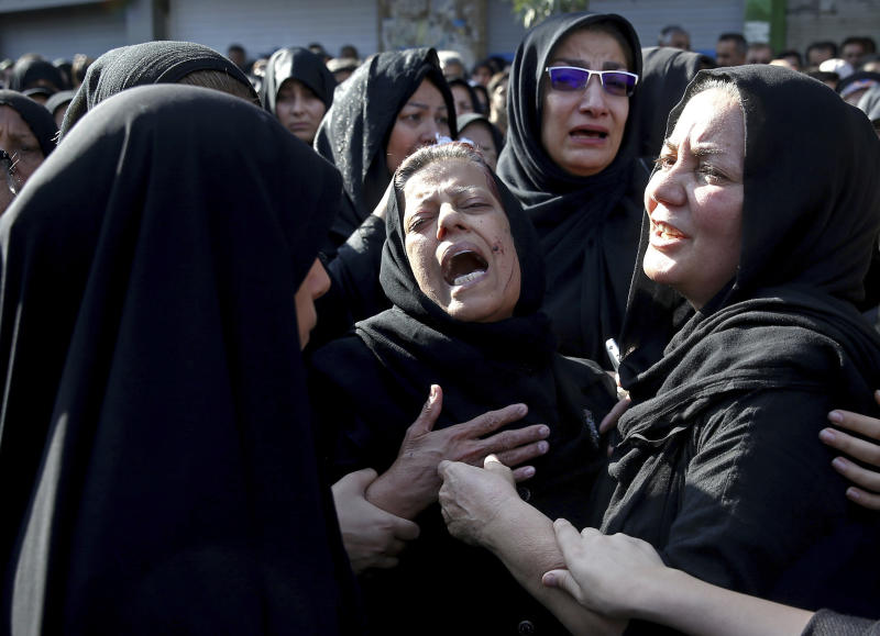 Families of victims of Saturday's terror attack on a military parade in the southwestern city of Ahvaz, that killed 25 people mourn at a mass funeral ceremony, in Ahvaz, Iran, Monday, Sept. 24, 2018. Thousands gathered at the Sarallah Mosque on Ahvaz's Taleghani junction, carrying caskets in the sweltering heat. (AP Photo/Ebrahim Noroozi)