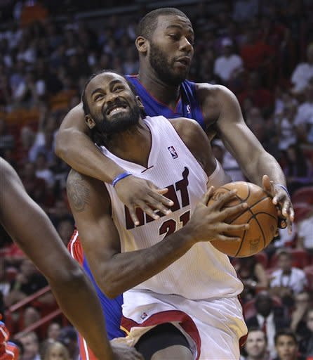 Detroit Pistons' Greg Monroe (10) fouls Miami Heats' Ronny Turiaf (21) during the first half of a NBA basketball game in Miami, Sunday, April 8, 2012. (AP Photo/J Pat Carter)
