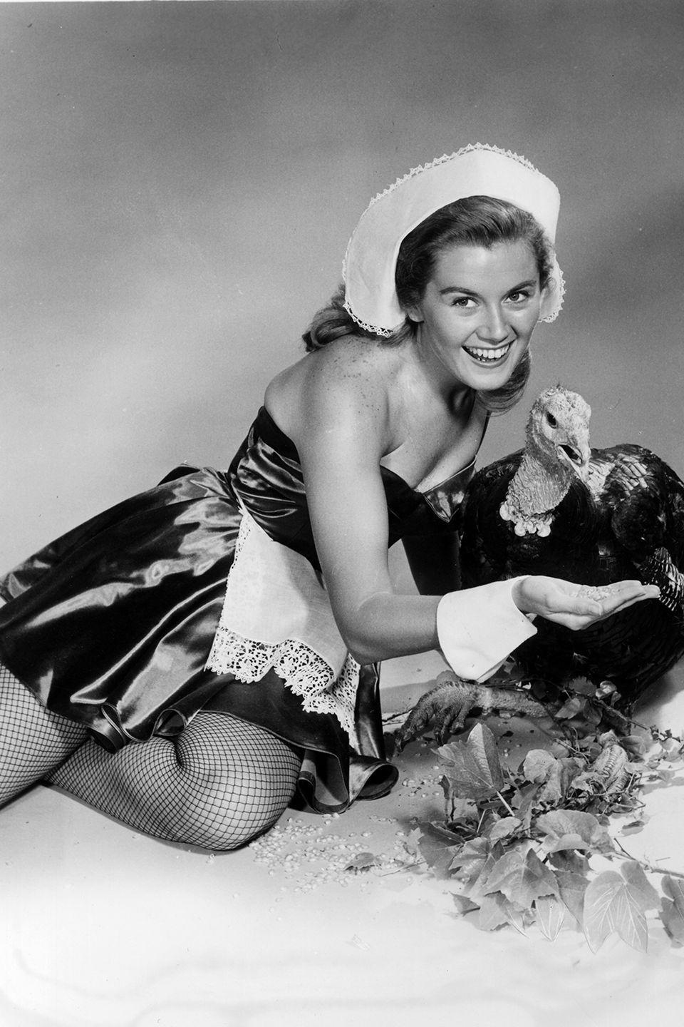 "<p>Pin-up photo shoots with Puritan-inspired outfits and live turkeys weren't uncommon in the '50s and '60s. Hollywood stars like <a href=""https://www.goodhousekeeping.com/life/entertainment/g28378198/rare-photos-of-marilyn-monroe/"" rel=""nofollow noopener"" target=""_blank"" data-ylk=""slk:Marilyn Monroe"" class=""link rapid-noclick-resp"">Marilyn Monroe</a> and Kathleen Nolan posed for such shots to be featured in Thanksgiving magazine spreads.</p>"