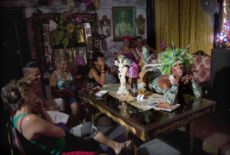 "In this May 15, 2013, Yanolis Carrero, 27, right, a gay transvestite artist known as ""Blanquita,"" performs on a table top during a drag show at the Fashion Bar Havana, in Havana, Cuba. A week of drag shows, colorful marches and social and cultural events in Havana culminates Friday with celebrations of the International Day Against Homophobia. Gays were persecuted for decades after the 1959 Cuban Revolution, sometimes sent to grueling rural work camps along with others considered socially suspect by the Communist government. But there has been a gradual shift away from macho attitudes, and Fidel Castro himself has publicly regretted the mistreatment of people seen as different. (AP Photo/Ramon Espinosa)"