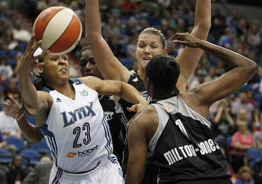 Minnesota Lynx forward Maya Moore (23) makes a quick pass around San Antonio Silver Stars forward DeLisha Milton-Jones (1) in the first half of a WNBA basketball game, Tuesday, June 11, 2013, in Minneapolis. (AP Photo/Stacy Bengs)